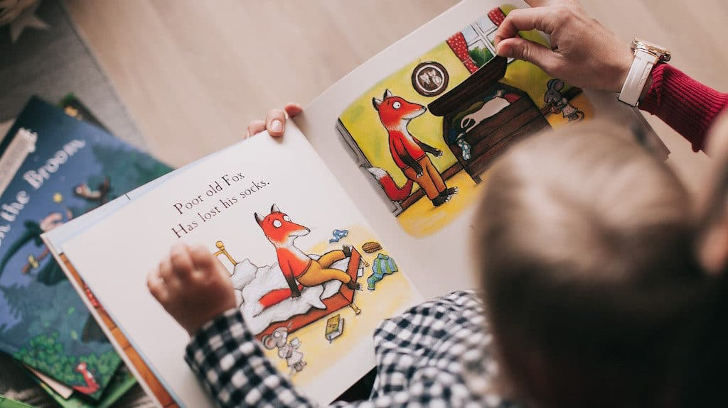 Parent and child reading a book with cartoon foxes.