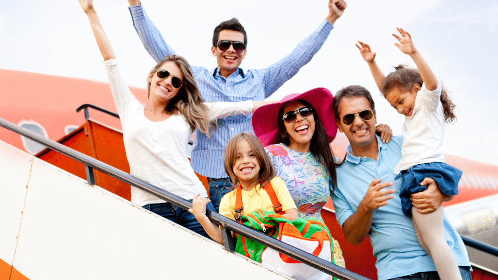 Family traveling with children pose outside of an airplane with arms up in excitement.