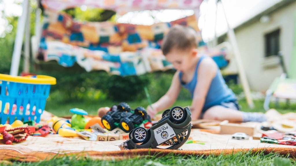 Child playing outside on the lawn with trucks, blocks paints and other toys.