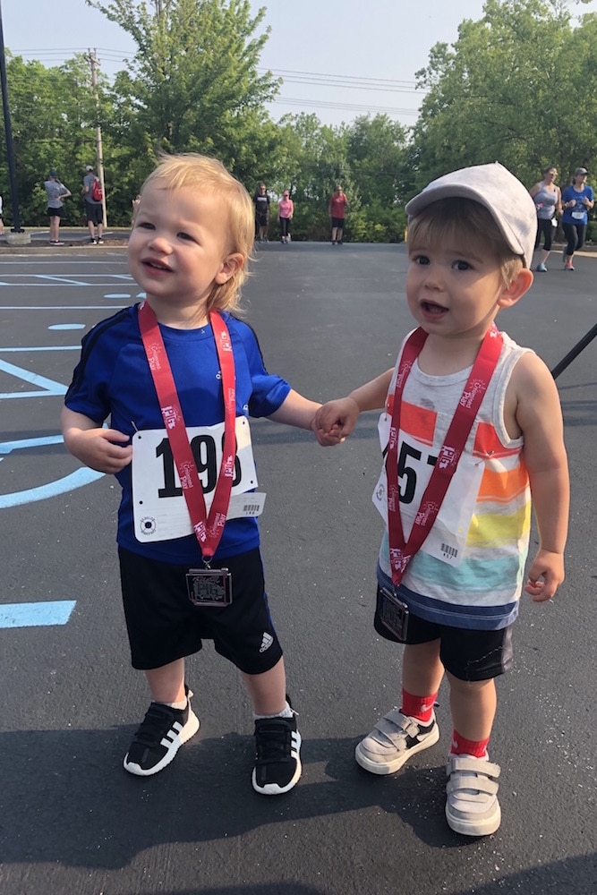Two toddlers hold hands as they proudly wear their race medals.