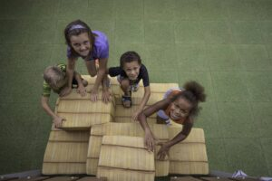 Children climbing on boxes towards camera
